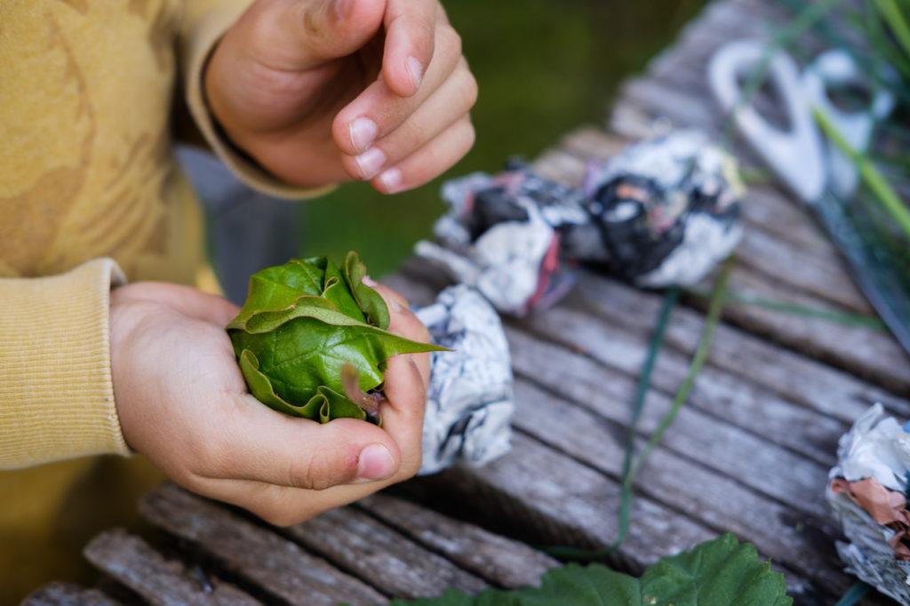 Grasbälle basteln: Die Bälle mit einem Blatt einwickeln