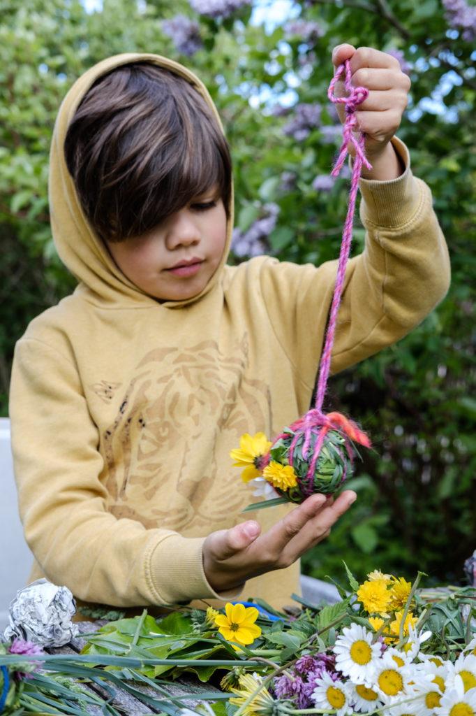 Grasbälle basteln: An bunten Fäden aufhängen